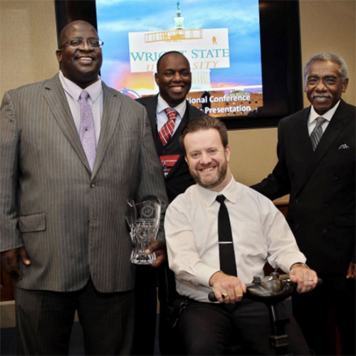 three African American men and man in wheelchair during awards ceremony